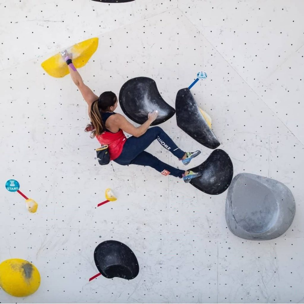 female climber climbing on a bouldering wall